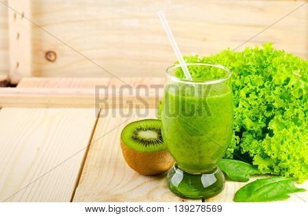 Healthy green smoothie with spinach, kiwi, apples, salad and mint in glass, on a wooden table
