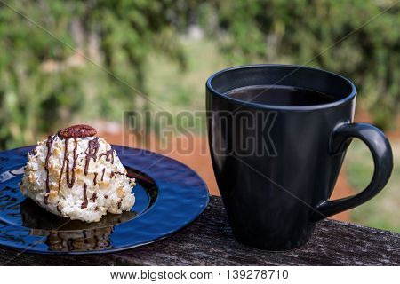 Coconut macaroon on a purple plate, sitting on a deck railing with black coffee mug