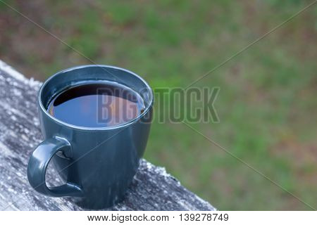 Close up of a black coffee cup on a deck railing, selective focus