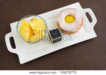 Fresh pineapple chunks and a lemon jelly filled donut on a white platter