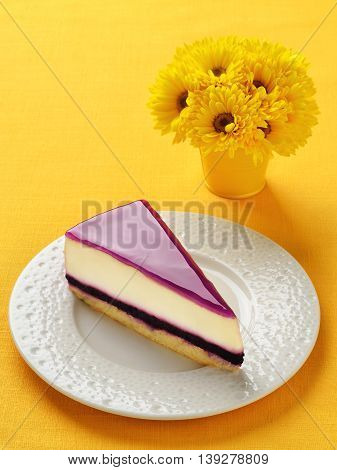 Blueberry cheesecake slice on plate. Yellow linen background.