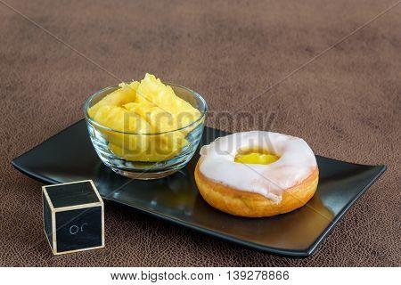 Fresh pineapple chunks and a lemon jelly filled donut on a black platter