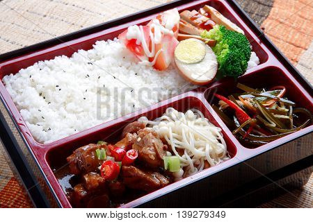 Bento food of plain rice and fried stewed pork eggs broccoli flower and seaweed