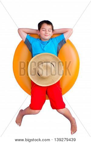 Cute barefoot young boy relaxing on a colorful bright orange inner tube or floaty with a straw sunhat on his stomach isolated on white conceptual of a summer vacation