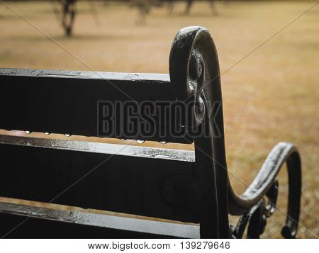 Close up of old curved steel and wooden vintage bench with water drop after rainy in blurry garden background Selective Focus