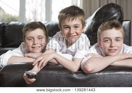 Three brothers hugging and playing on the sofa