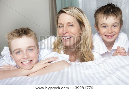 A Mother And two Son Relaxing Together In Bed