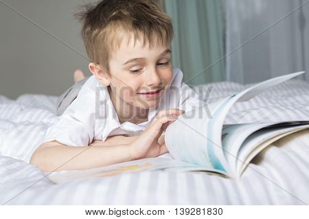 A little boy reading before dream in his bed