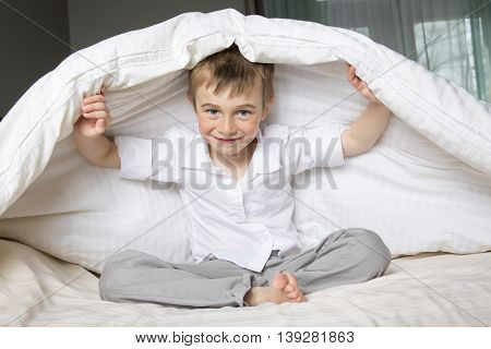 A Smiling boy hiding in bed under a white blanket or coverlet.