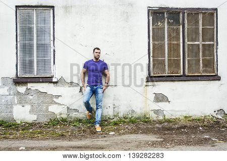 An Attractive young man is standing on the street wall