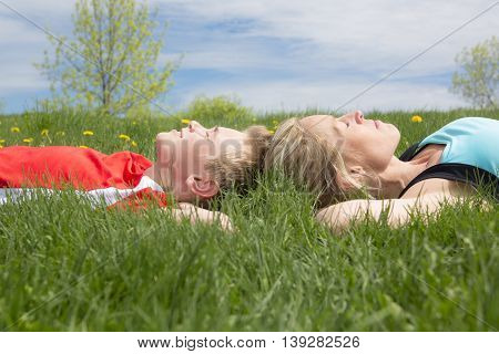 A mother and son laying on the grass