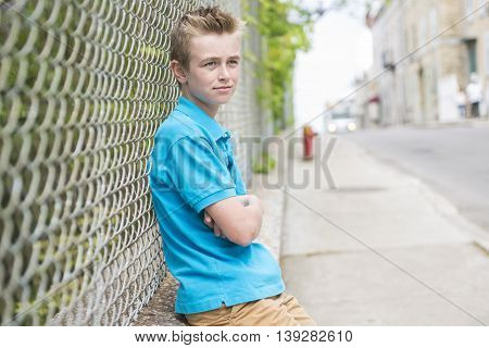 A young teen boy looking out of a fence