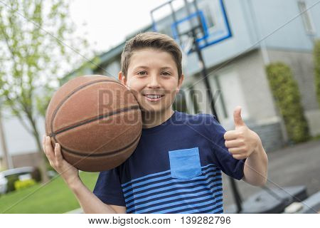 A Boy with a ball outside in fron of his house