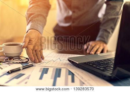 businessman working use laptop in office for discussing documents and ideas with soft focus vintage tone