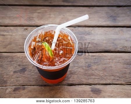A glass of ice lemon tea on wooden table