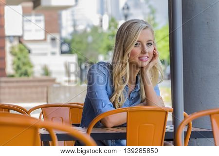 A blonde model sitting at a cafe in a city setting