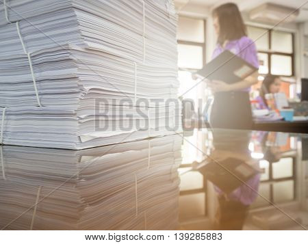 Pile of unfinished documents on office desk with businesswoman background