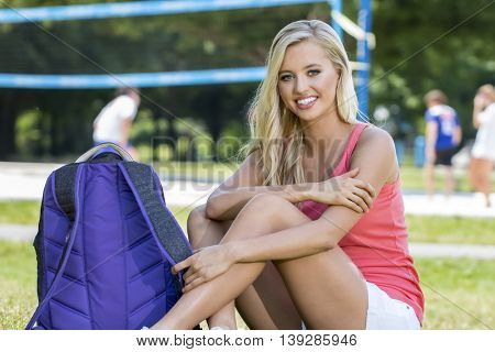 A blonde model posing in an outdoor environment