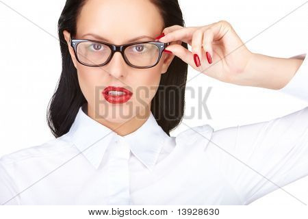 Gorgeous woman with red lips touching eyeglasses while looking at camera