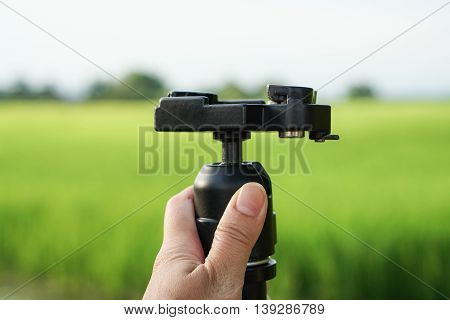 Close up hold camera tripod by human hand with green field background