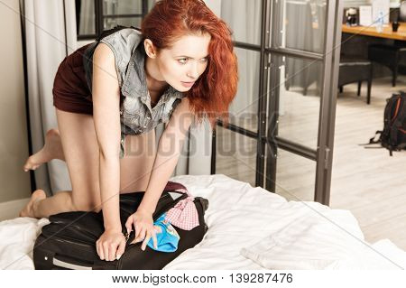 Attractive Red-haired Young Woman Packing A Travel Bag Before Going On Holiday