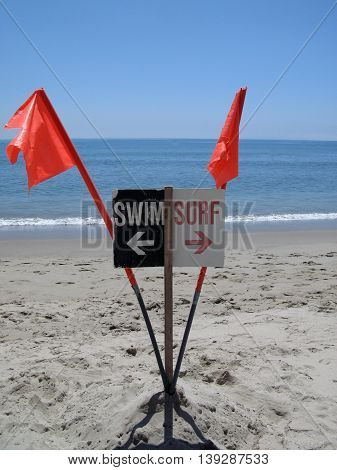 Sign on beach with orange flags designates separate areas for swimming and surfing in Malibu, California.