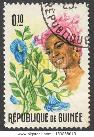 MOSCOW RUSSIA - CIRCA JANUARY 2016: a stamp printed in GUINEA shows a woman in the traditional headdress and a plant Clitoria sp. the series