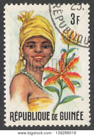 MOSCOW RUSSIA - CIRCA JANUARY 2016: a stamp printed in GUINEA shows a woman in the traditional headdress and a plant Gloriosa sp. the series