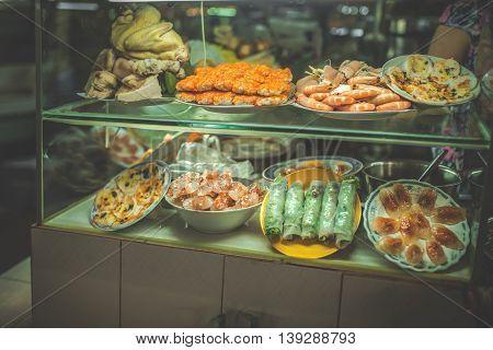 Food vendor in Saigon Vietnam. Traditional spring rolls.