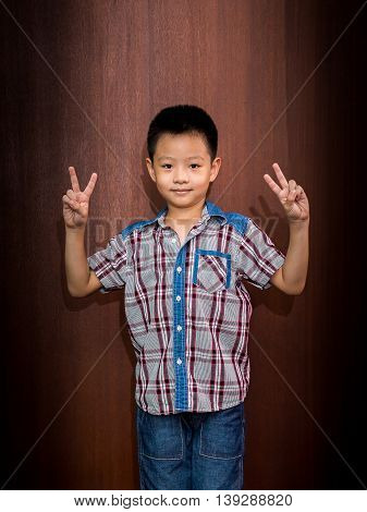 Portrait of happy little boy showing fingers or victory gesture