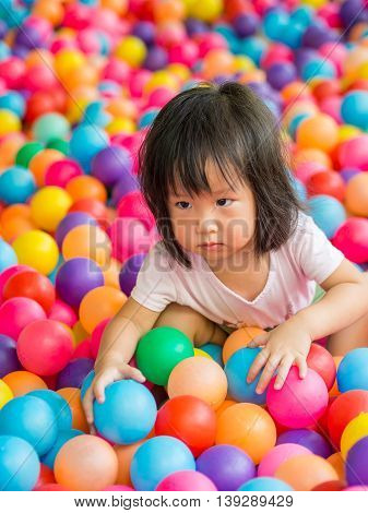 Happy little Asian girl playing with balls
