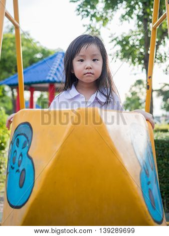 Happy kid asian baby child in school uniform playing on playground