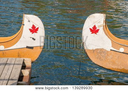 Ends of two canoes with copyspace and canadian red maple leaf