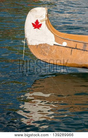 End of a white canoe with copyspace and canadian red maple leaf