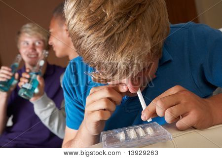 Group Of Teenage Boys Taking Drugs At Home