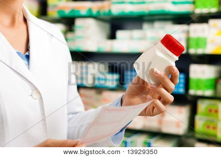 Female pharmacist � only hands to be seen � standing in pharmacy with pharmaceuticals