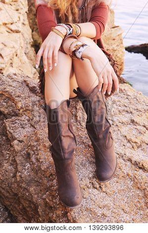 Female hands with white manicure and boho chic bracelets and legs dressed in leather boots, woman sitting on a rock in a sea, outdoor fashion photo, autumn colors