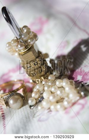 old family jewels with pearl rings and necklace and combination padlock