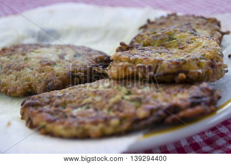 battered and fried zucchini fritters on absorbent paper
