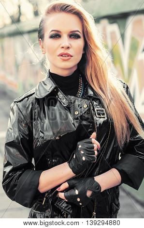 Young sexy glamour blonde woman wearing total black outfit sunglasses and leather jacket walking at the street vintage colors urban style.