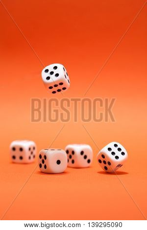 Dice game. One dice cube falling to another dices on red background