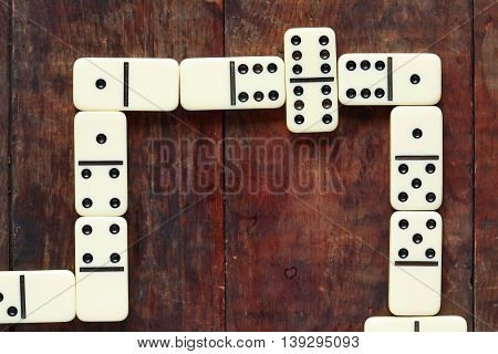 Gambling concept. Domino game closeup on nice old wooden background