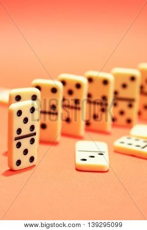 Black dominoes standing in a row on red background