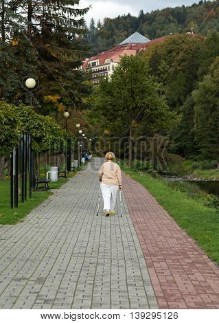 Senior woman doing nordic walking in Wisla Poland