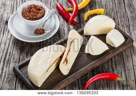 homemade mozzarella stuffed with adjika or red pesto hot and spicy with chili and sauce in gravy boat on wooden background close-up