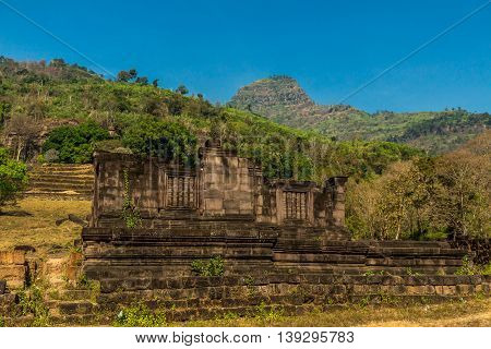 Crumbling ruins of a Khmer temple under a mountain in Laos