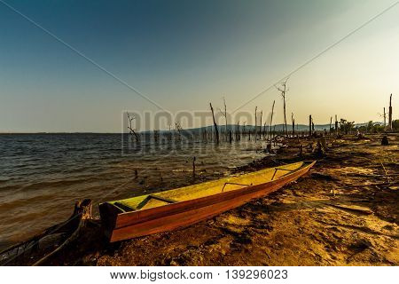 A boat on the desolate shore of a new reservor as the sun goes down in rural Laos