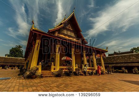 A monk talks to two people at the golden Wat Si Saket in Vientiane, Laos