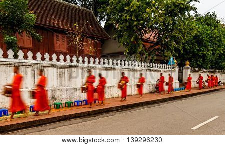 Orange robed buddhist monks walk down the street in Luang Prabang, Laos duing the daily alms ceremony