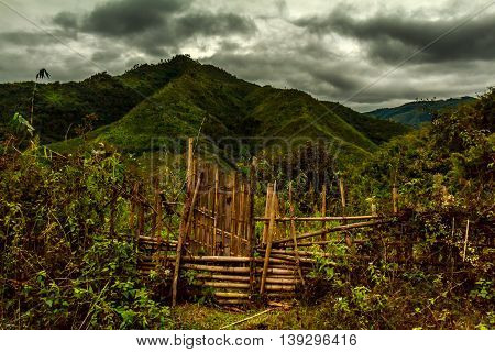 A scenic wooden fence and green hills on a stormy day in Laos